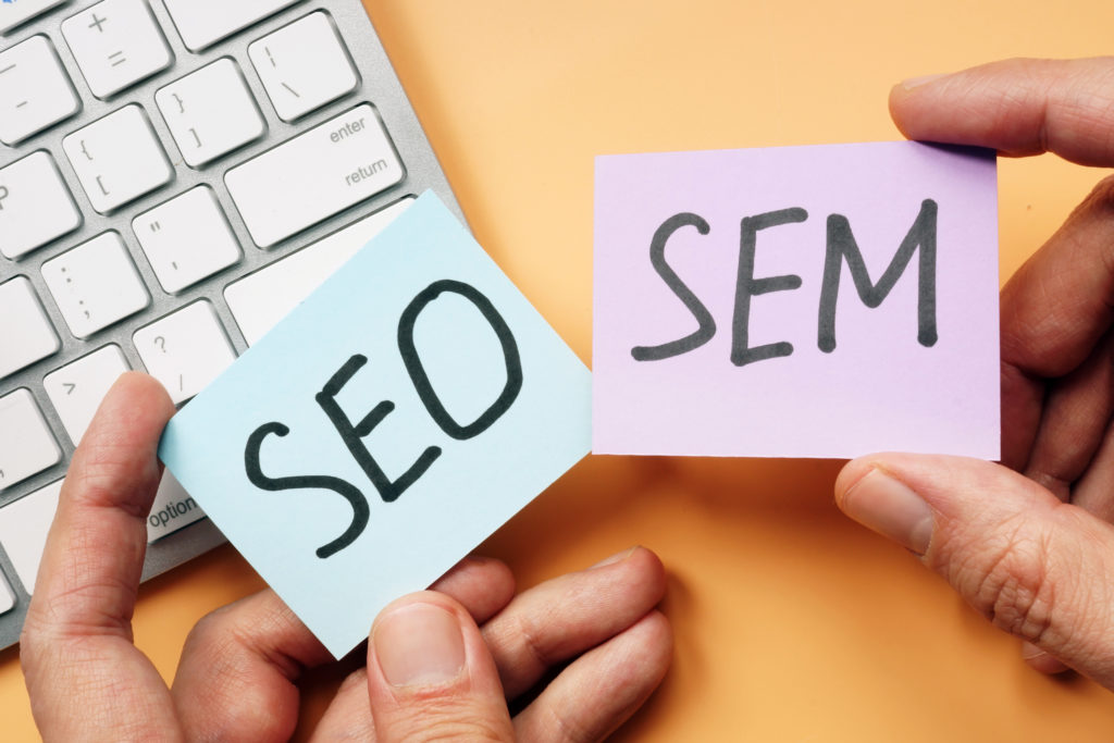 Man at laptop holding two post it notes. One says SEO the other says SEM.